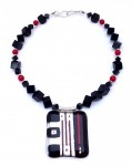 Fused-glass pendant with red lines in a necklace of square beads