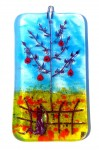 Glass decoration of red apple tree in flowery field with cat on fence