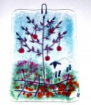 Glass decoration of red apple tree in flowery field with sheep